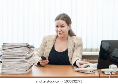 Office-girl white-collar worker Caucasian woman sitting at table with pile of documents
