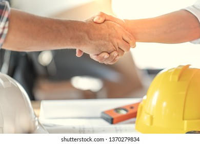 Officer teamwork is happy and shake hands to celebrate in success of finish in job planning about home building construction project