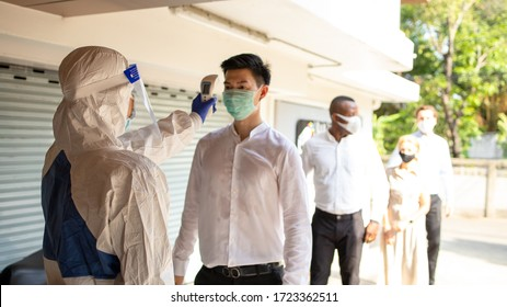 Officer wearing a respirator mask to use infrared forehead thermometer to check fever body temperature for virus symptoms. Respiratory diseases such as flu, covid19, coronavirus. Epidemic outbreak