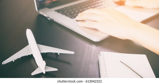 Officer worker is working on Travel agency office desk with computer and plane. A person is planning his Vacation holidays travel online.
