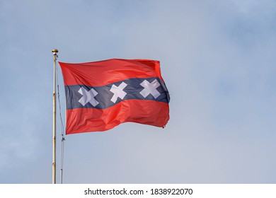 Official flag of Amsterdam waving on the air in a sunny day and blue sky background, The flag depicts three Saint Andrew's Crosses and is based on the escutcheon in the coat of arms of Amsterdam.