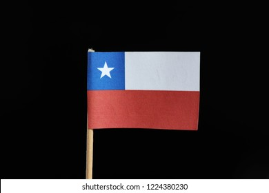 A official flag of Chile  on toothpick on black background. A horizontal bicolor of white and red with the blue square ended on the upper with white star.