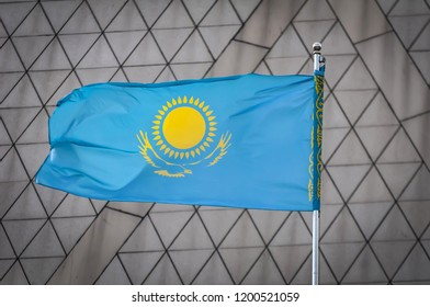 The official flag of the Republic of Kazakhstan waving in the sky against a triangles background. Kazakh flag and statehood concept.