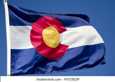 The official flag of the state of Colorado waves boisterously against a brilliant blue sky.  This state sits in the middle of the United States, with the Rocky Mountains running through its center.