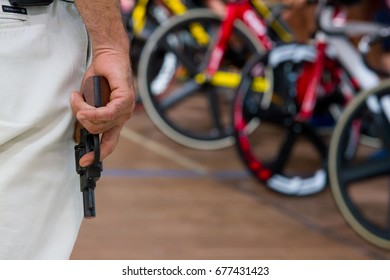 An official holds a pistol to give the signal for the bicycle race to start.