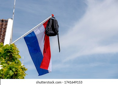 Official Netherlands flag with a school bag hanging out side the house, A tradition way in Holland when a student celebrate their graduates or Geslaagd in Dutch word, Netherlands.