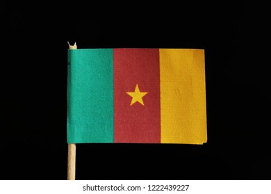 A official and original flag of Cameroon on toothpick on black background. It is a vertical tricolor of green, red and yellow with a five-pointed star in center.