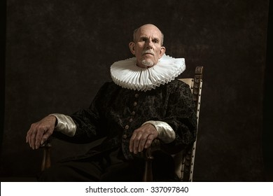 Official portrait of historical governor from the golden age. Sitting in chair. Studio shot against dark wall.