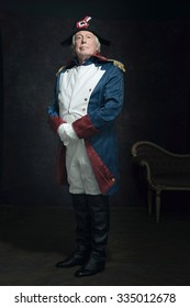 Official portrait of senior man dressed in historical emperor costume. Studio shot against dark wall.