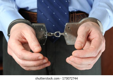 Official's hands in handcuffs