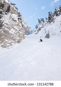Off-piste skier in a steep chute in Chamonix, France.