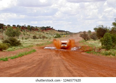 Offroad 4x4 camper van driving through deep puddle floodway in australia outback with mudd water splashing from the tires