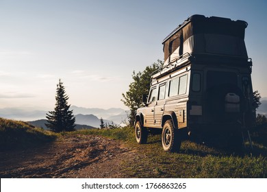 Off-road 4x4 with pop top elevating roof sleeping tent storage vehicle on the dirty country road in the Slovakian mountains in the early morning sunrise time.