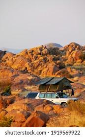 Geländewagen 4x4 mit Zelt auf dem Dach, das zum Zelten in der Wüste bereit ist