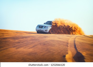 Off-road adventure with SUV in Arabian Dubai Desert at sunset. Offroad vehicle bashing through sand dunes in Dubai desert. Dune bashing attraction for tourists.