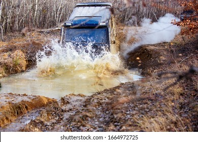 Offroad car in action. SUV wheels in mud and water. Outdoors adventures. Dirty offroad tire covered with mud. Offroad. 4x4 off-road suv car stuck in mud