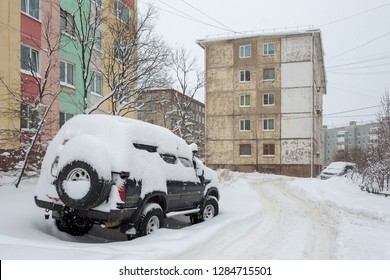 Offroad car covered with snow after a snowfall. Snowdrifts around on the road and in the yard. Snow on the roof and windows of the car. In the background panel buildings. Magadan, Far East of Russia.