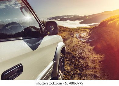 Offroad Car On Mountains And Clouds Background. Road Adventure Holidays Vacation Concept