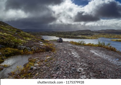 Off-road car on the stoned road in the tundra at rain weather