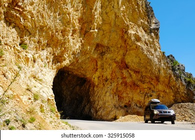 Off-road car is standing on the road near mountain rocks. Outdoor, adventures and travel suv. Expedition, explore and wanderlust lifestyle. Countryside landscape.