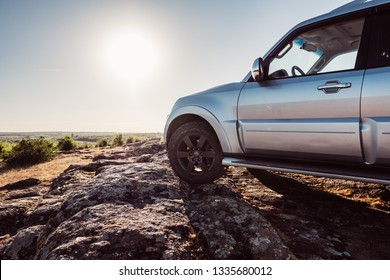 Off-road car is standing on rocky mountain road. Outdoor, adventures and travel suv. Expedition, explore wheels on summer path way. Car tyre tracks on countryside nature landscape stones.