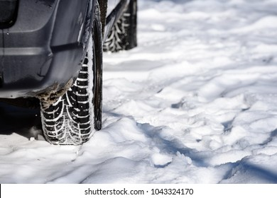offroad car tires stuck in the snow in with snowy road laying ahead. mirrors and headlights in foreground