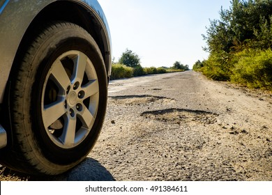 Off-road car wheels on damaged road, cracked asphalt blacktop with big holes, Ukraine. Tire on bad tarmac road. Outdoor, adventures, expedition, and travel suv. Close-up car tyre tracks.