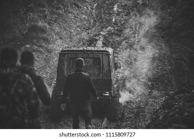 off-road. Company of three men looks at suv drives with clouds of smoke. Car covered with mud on path with deep rut. Offroad car with dirt on background. Extreme entertainment concept.