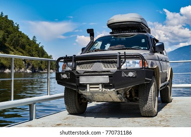 Offroad expedition car stands on ferry against the background of wooded mountains, sunny sky and water.