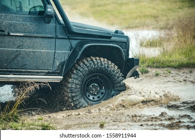 Off-road Jeep car on bad gravel road. Mud and water splash in offroad racing. Off-road travel on mountain road