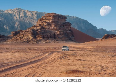 off-road jeep going through incredible lunar landscape in Wadi Rum village in the Jordanian red sand desert. Wadi Rum also known as The Valley of the Moon,  Jordan - Image