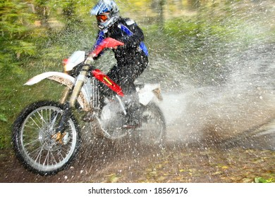 Off-road motorbike crossing river, water splashing. Motion blur.
