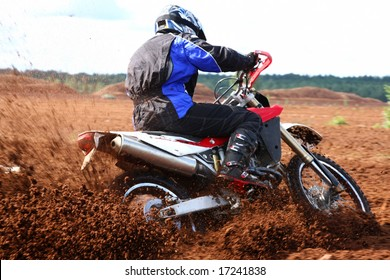 Off-road motorbike extreme cornering. Motion blur with flying dirt.