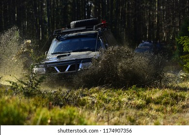 Offroad race on fall nature background. Cars racing in autumn forest. SUV or offroad car on path covered with grass crossing puddle with dirt splash. Extreme, challenge and 4x4 vehicles concept.