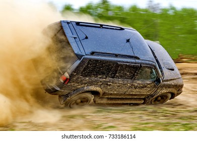 Off-road racing. Rally car. The car skidded on a wet road. Car creates a large cloud of dirt and dust. Off-road.