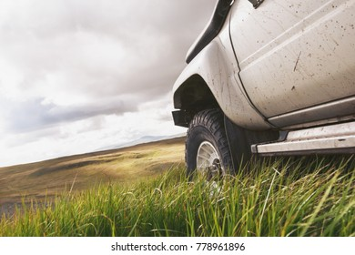Offroad ready car after dirty road on green grass. Closeup photo of big car wheel