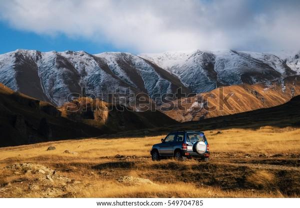 Off-road roadtrip reizen met auto op bergweg tegen rotsen en gletsjer in de Kaukasus, Georgië. Mooie lichten en kleuren bij zonsondergang