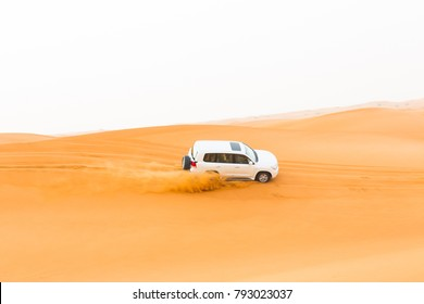 Off-road SUV vehicle speeding through sand dunes in the Arabian desert.