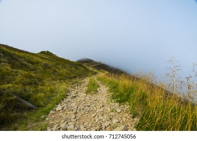 Off-road trail in the mountains disappearing in the fog