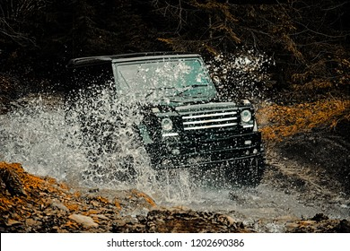 Off-road travel on mountain road. Mud and water splash in off the road racing. Drag racing car burns rubber. Extreme. Off-road car. 4x4 travel trekking. Rally racing