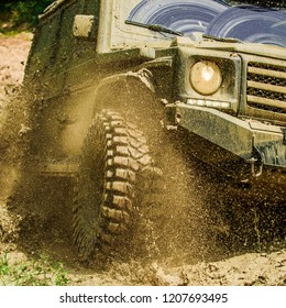 Off-road travel on mountain road. Travel concept with big 4x4 car. Mud and water splash in off-road racing. Motion and power concept