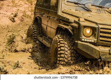 Off-road travel on mountain road. Bottom view to big offroad car wheel on country road and mountains backdrop. Drag racing car burns rubber. Extreme. Off-road car