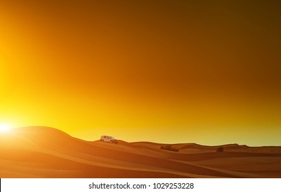 Offroad truck or suv riding dune in arabian desert at sunset. Offroad has been modified to be unrecognized.