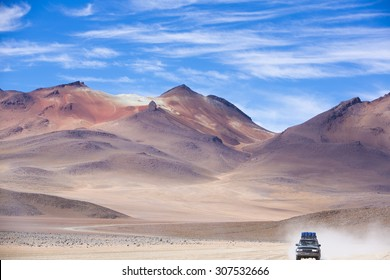 Off-road vehicle driving in the Atacama desert, Bolivia with majestic colored mountains and blue sky in Eduardo Avaroa Andean Fauna National Reserve, Bolivia