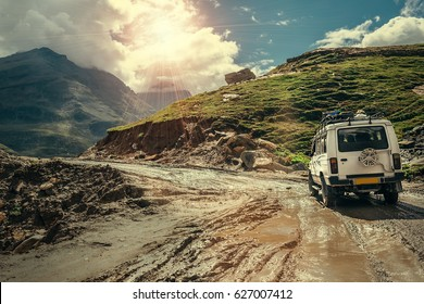 Off-road vehicle goes on the mountain way during the rainy season