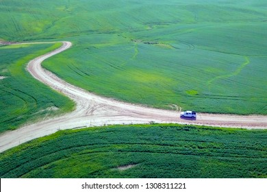 Off-Road Vehicle on a dirt track in a lush green Badlands terrain - Top down aerial follow image.