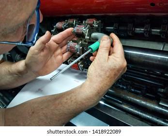 Offset machinist preparing a set of offset numerators
