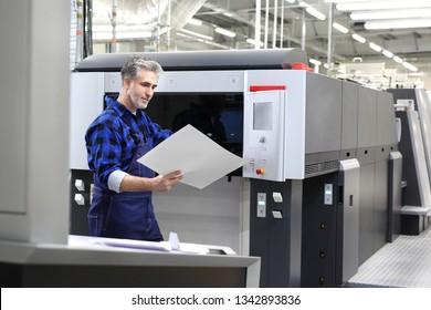 Offset printing. The printer checks the printout. Printer in the printing house.