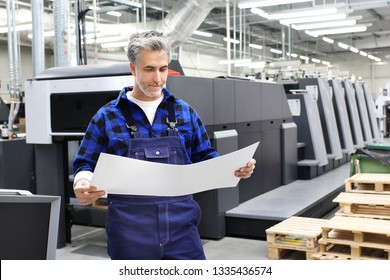 Offset printing. A printer with a printout sheet is standing in front of the printing machine.