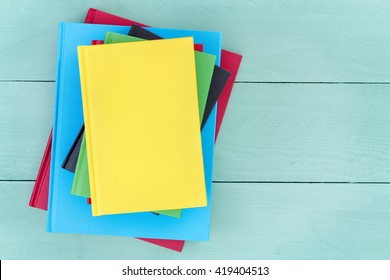 Offset stack of multicolored hardcover books piled up on a stained pastel colored green wood table with a bright yellow book on top and copy space to the side, overhead view